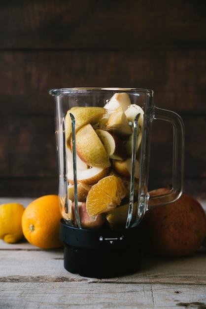 Misturador cheio de mix de frutas na mesa de madeira Foto gratuita