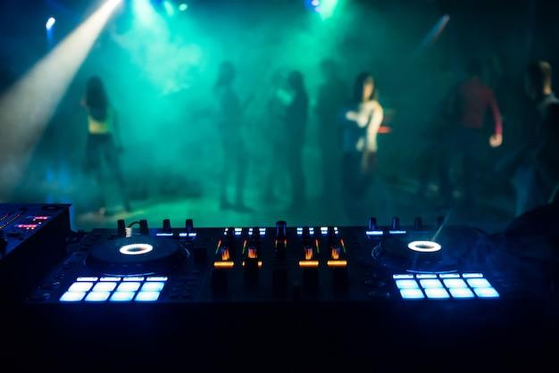 Misturador de música no estande do dj na boate com as pessoas na pista de dança e atmosfera de noite Foto Premium