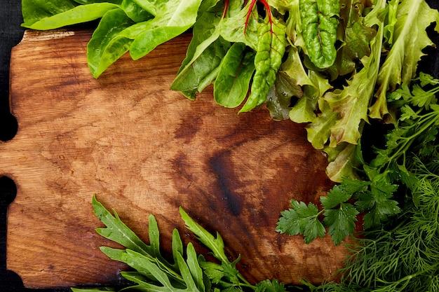 Misture a salada da folha na placa de corte de madeira. Foto Premium