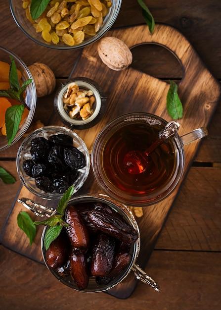 Misture frutas secas (tâmaras, ameixas, damascos, passas) e nozes e chá árabe tradicional. comida do ramadã (ramazan). vista do topo Foto Premium