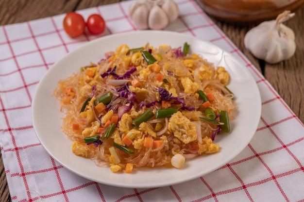 Misture o macarrão de vidro frito com os ovos e coloque em um prato sobre um pano branco vermelho. Foto gratuita