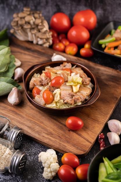Misture o repolho com barriga de porco em um prato sobre uma placa de madeira. Foto gratuita