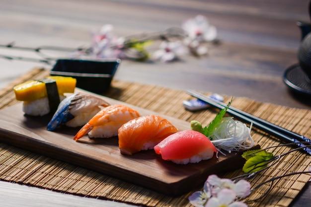 Misture o sushi no prato de madeira, atum, salmão, robalo, ovo doce, sushi de camarão, comida japonesa Foto Premium