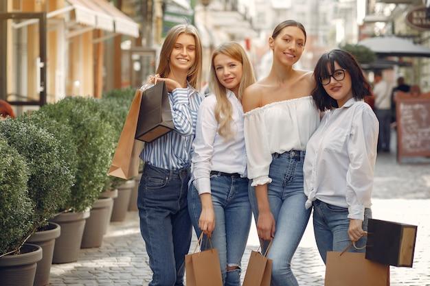Miúdas giras com sacola de compras em uma cidade Foto gratuita