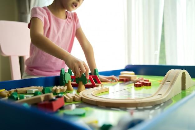 Miúdo bonito asiático pequeno novo que joga o brinquedo de madeira na tabela em casa. Foto Premium