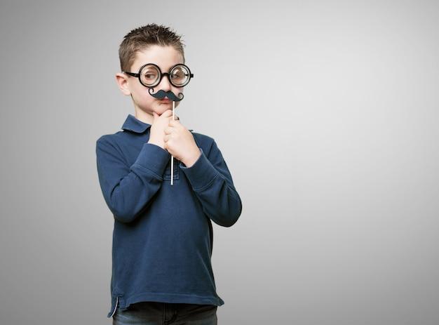 Miúdo com óculos e bigode falso Foto gratuita