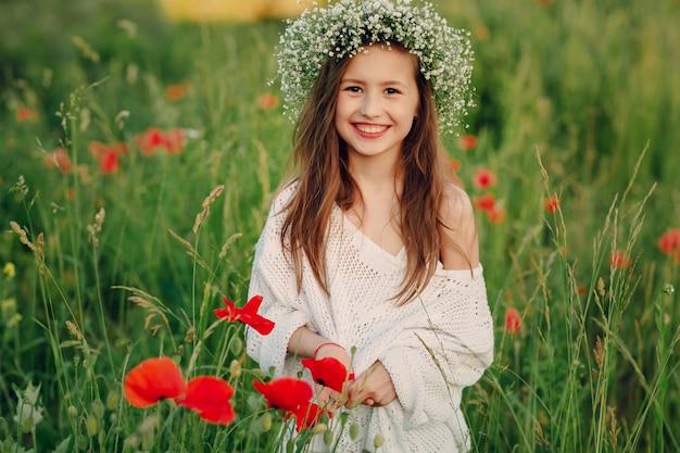 Miúdo de sorriso que desgasta uma grinalda Foto gratuita