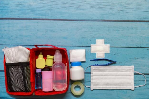 Miúdo do saco dos primeiros socorros da vista superior com subministros médicos no fundo de madeira. Foto Premium