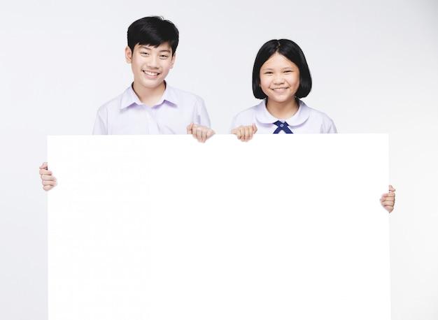 Miúdos asiáticos bonitos no uniforme do estudante com placa branca. Foto Premium