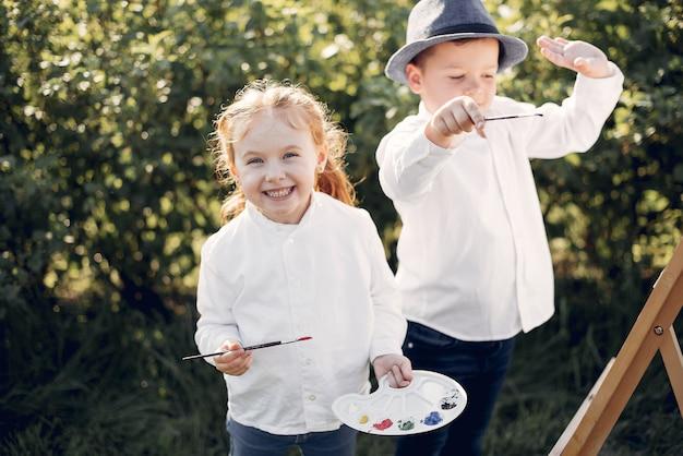 Miúdos bonitos que pintam em um parque Foto gratuita