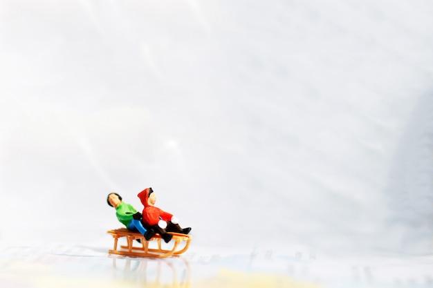 Miúdos diminutos que jogam o divertimento com slider da neve. Foto Premium