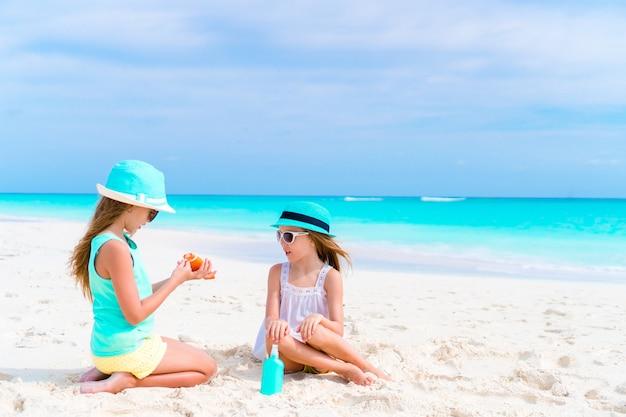 Miúdos que aplicam o creme do sol a se na praia. o conceito de proteção contra radiação ultravioleta Foto Premium