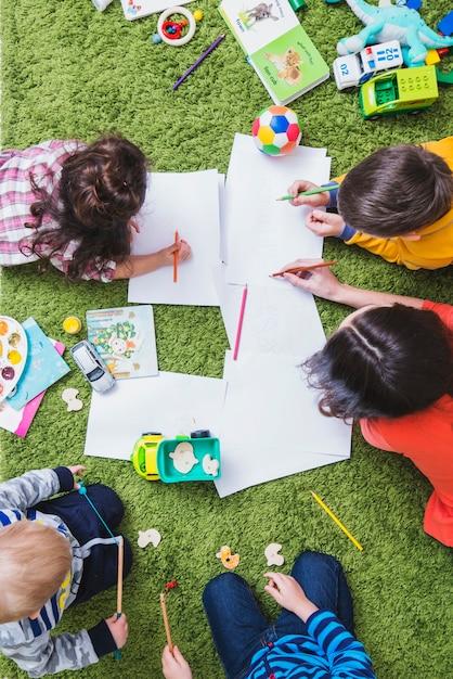 Miúdos que desenham e que jogam Foto gratuita
