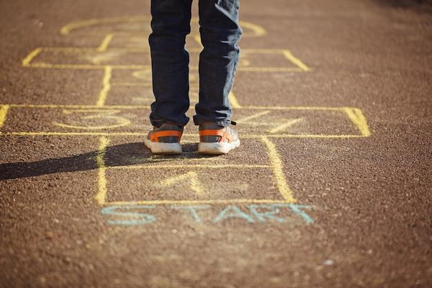 Miúdos que jogam amarelinha no campo de jogos ao ar livre. jogo de rua popular amarelinha Foto Premium