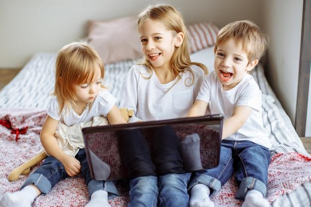 Miúdos que jogam com computador portátil em casa Foto Premium