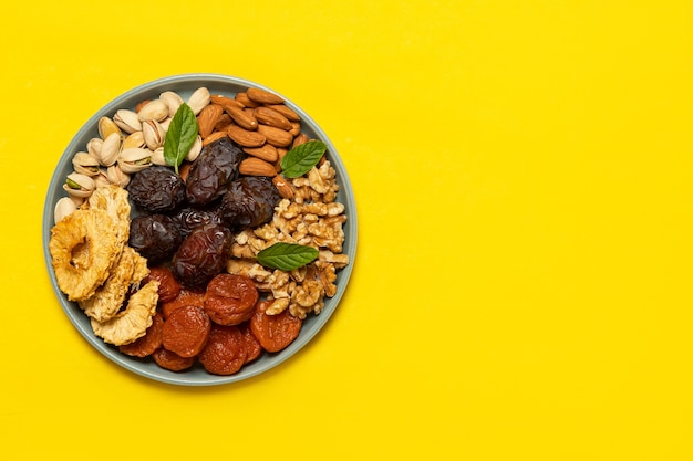 Mix de frutas secas e nozes em um prato em fundo amarelo com espaço de cópia. vista de cima. símbolos do feriado judaico de tu bishvat Foto Premium