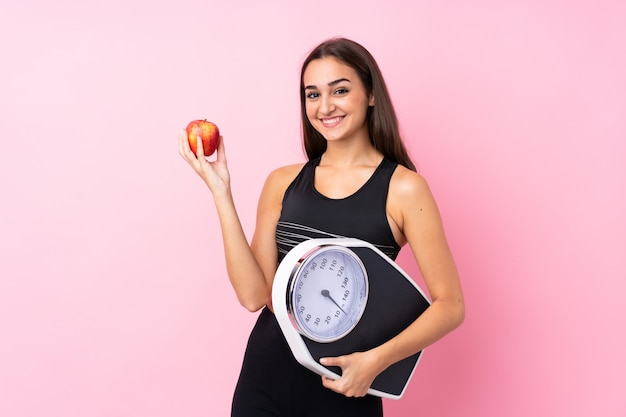 Moça bonita com máquina de pesagem com máquina de pesagem e com uma maçã Foto Premium