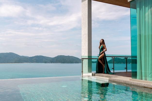 Moça bonita em um vestido verde longo posando perto de uma piscina ao ar livre com vista para o mar e montanhas verdes Foto Premium