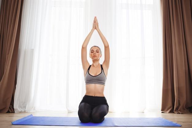 Moça bonita faz exercícios de ioga no chão Foto gratuita