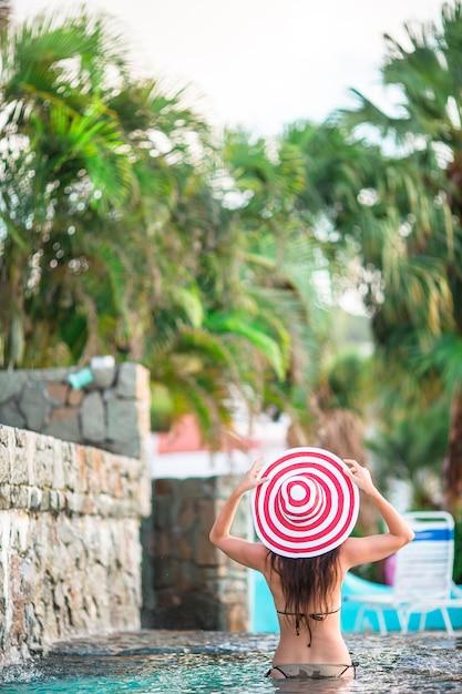Moça bonita que relaxa na piscina ao ar livre Foto Premium