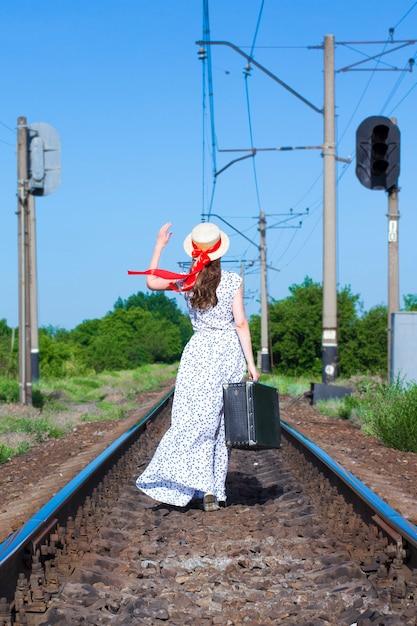 Moça com a mala velha nos trilhos. uma garota bonita está andando com uma mala. a vista de trás. um adolescente em um chapéu de canapés com uma fita vermelha e um vestido longo. Foto Premium