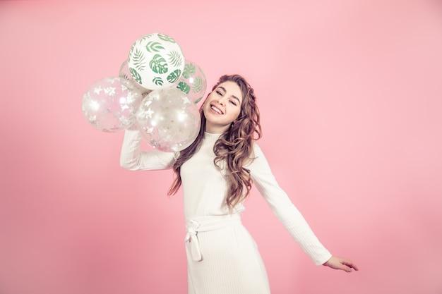 Moça com balões em uma parede colorida Foto gratuita