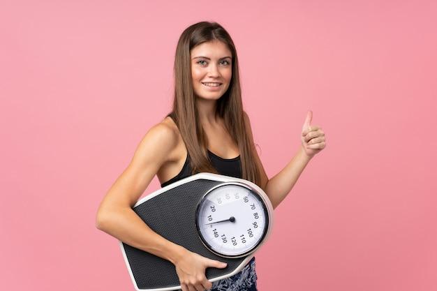 Moça com máquina de pesagem e com o polegar acima sobre rosa isolado Foto Premium