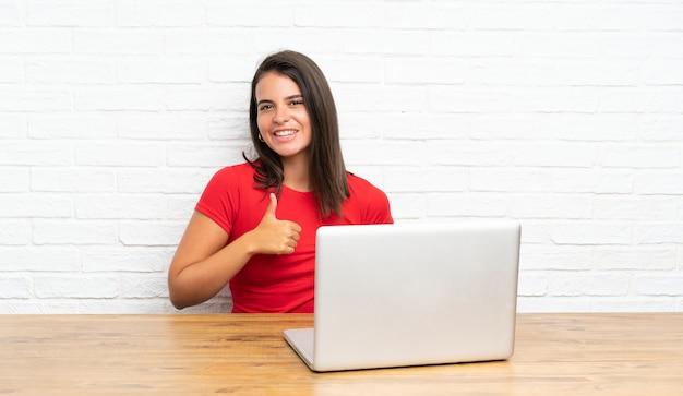 Moça com pc em uma tabela dando um polegar para cima gesto Foto Premium