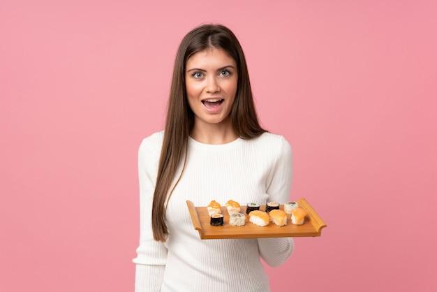 Moça com sushi isolado sobre com surpresa e expressão facial chocada Foto Premium