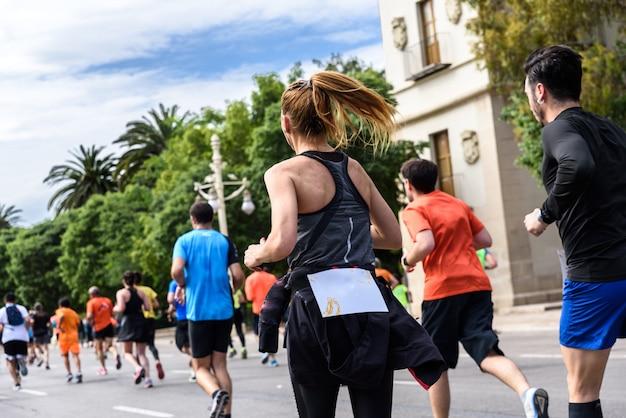 Moça consideravelmente loura que executa o exercício em uma raça running cercada por outros corredores. Foto Premium