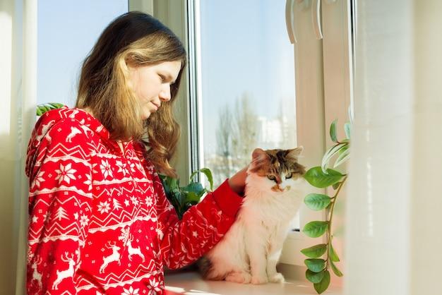Moça de pijama quente com gato Foto Premium