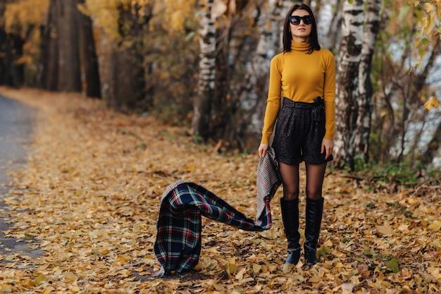 Moça elegante e confortável caminhar no parque outono colorido em óculos de sol Foto Premium