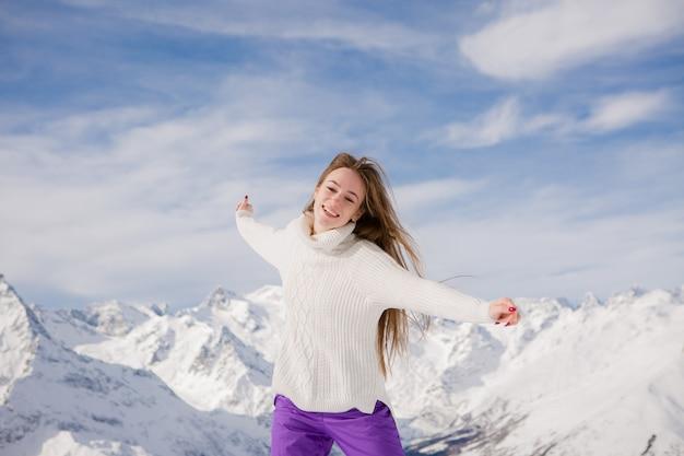 Moça em um terno de inverno que sorri nas montanhas Foto Premium