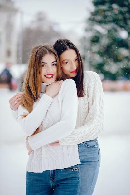 Moça em uma camisola branca que está em um parque do inverno Foto gratuita