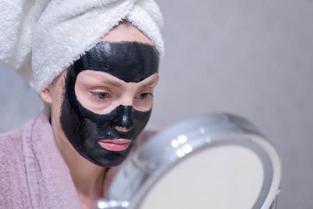 Moça em uma máscara preta de limpeza do carvão em sua cara. Foto Premium