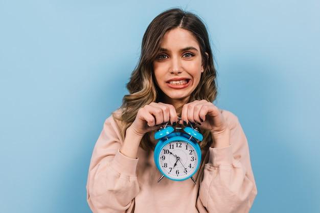 Moça engraçada posando com um grande relógio Foto gratuita
