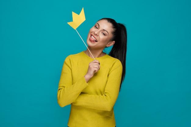 Moça engraçada que mantém a coroa de papel e mostrando a língua Foto Premium
