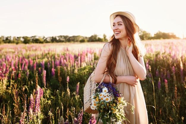 Moça feliz que anda no campo de flor no por do sol. vestindo chapéu de palha e bolsa cheia de flores. Foto gratuita