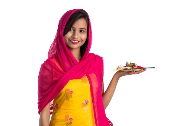 Moça indiana bonita que guarda pooja thali ou que executa a adoração Foto Premium