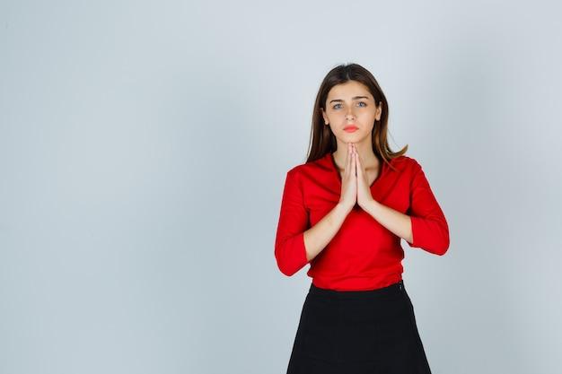 Moça mostrando as mãos postas em gesto de súplica com blusa vermelha Foto gratuita