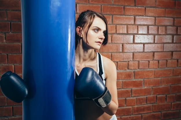 Moça nas luvas que descansam após um exercício no gym do encaixotamento Foto Premium