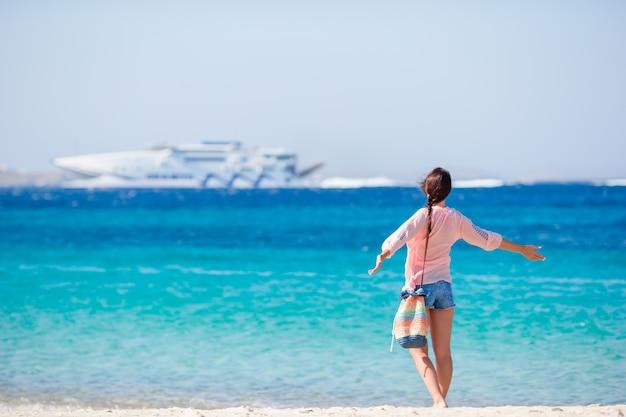 Moça no forro grande do cruzeiro do fundo da praia. a mulher aprecia seu wekeend em uma das praias bonitas em greece, europa. Foto Premium