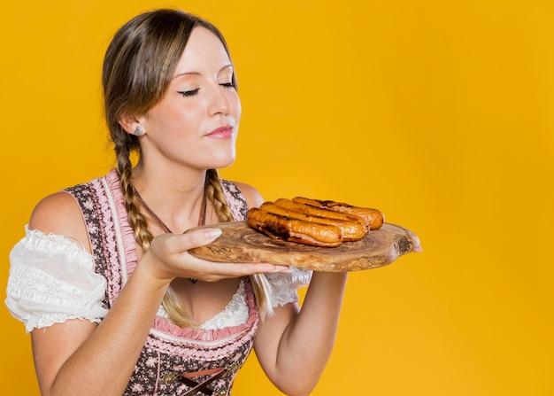 Moça positiva que guarda salsichas Foto gratuita