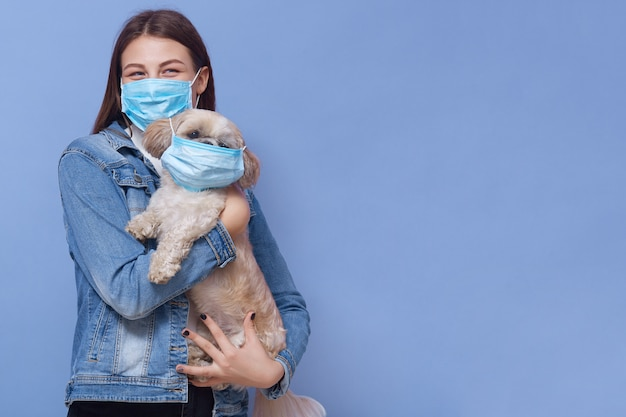 Moça que desgasta a máscara médica com seu animal de estimação Foto gratuita