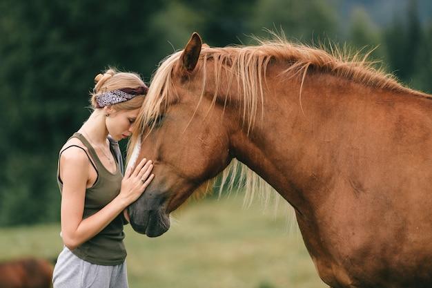 Moça que está cara a cara com um cavalo. Foto Premium
