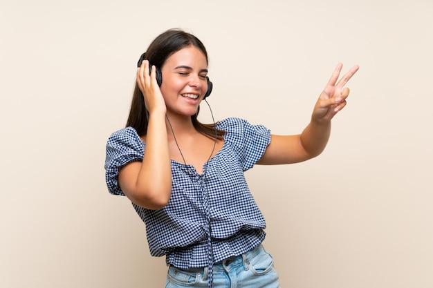 Moça sobre parede isolada, ouvindo música com fones de ouvido Foto Premium