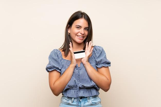 Moça sobre parede isolada, segurando um cartão de crédito Foto Premium