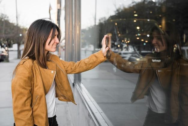 Moça sorridente com a mão na vitrine Foto gratuita