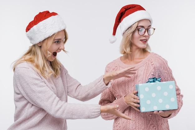 Moças bonitas com uma caixa de presente Foto gratuita