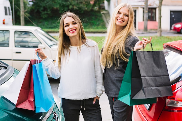 Moças bonitas que estão fora da rua que guardara sacos de compras à disposição Foto gratuita